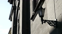 Three lamps of street lighting are fastened on the wall of old building in Stock Footage