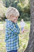 Children playing hide and seek outdoors Stock Photos