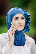 Woman in headscarf talking on cell phone - stock photo