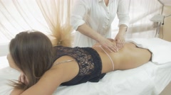 Masseuse make massage of gluteus to girl in thong, black top in beauty saloon Stock Footage