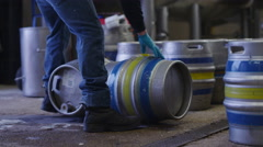 4K Worker in a brewery preparing barrels of beer to be filled - stock footage