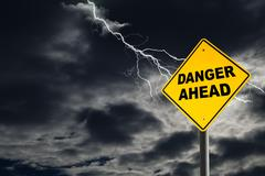Danger Ahead Sign Against Cloudy and Thunderous Sky - stock photo
