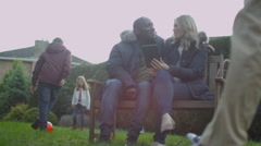 4K Large mixed ethnicity family & friends group spending time outdoors in garden Stock Footage