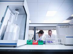 Scientists in laboratory with samples and analytical scientific equipment Stock Photos