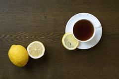 Tea with lemon on wooden board - stock photo
