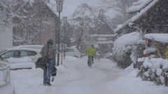 Two men walking and biking on a street covered with snow in Hallstatt Stock Footage