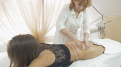 Masseuse make rigid massage of gluteus to girl in thong, top in beauty saloon Stock Footage