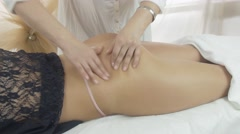 Masseuse make massage of gluteus to young girl in beauty saloon. Tingling Stock Footage