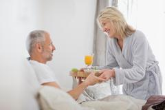 Woman bringing husband breakfast in bed Stock Photos