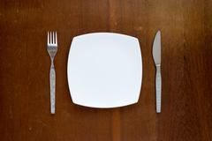 Plate, fork and knife on wooden background Stock Photos