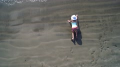 Aerial view of little girl writing in the sand   4K Stock Footage