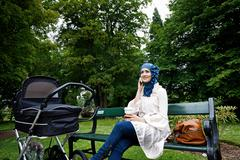 Woman in headscarf with stroller in park - stock photo