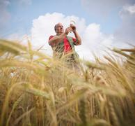 Farmer with barley (Hordeum vulgare) in field Stock Photos