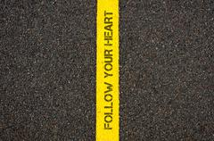 Road marking yellow line, text FOLLOW YOUR HEART Stock Photos