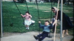 3180 mom pushes her children on the swing - vintage film home movie Stock Footage