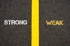 Antonym concept of STRONG versus WEAK - stock photo