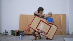 Father teaching little adorable son how to make a wooden basketball board - stock footage