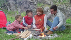 Mother, father, son and little daughter making bread over campfire and talking Stock Footage