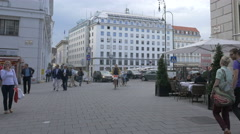 Walking and riding bikes on Bognergasse, near Am Hof square, Vienna Stock Footage