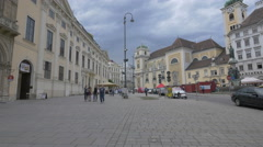 People walking in a square near the Schottenstift monastery, Vienna Stock Footage