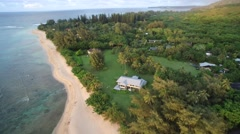 Aerial view of house sitting on edge of beach Stock Footage