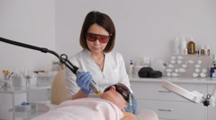 Cosmetician in safety glasses using laser for facial treatment in cosmetology Stock Footage