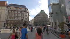 Young and old people walking in Stephansplatz on a sunny day in Vienna Stock Footage