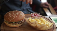Set of classic american cheese burger and french fries in hands Stock Footage