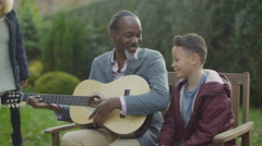 4K Family group outdoors in garden, grandfather plays guitar for grandson Stock Footage