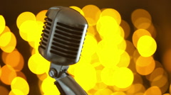 Retro microphone against colourful background Stock Footage