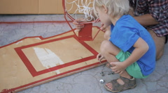 Father teaching son how to screw bolt into wooden basketball board - stock footage