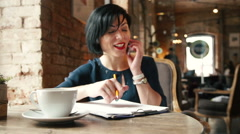 Candid image of a businesswoman working in a cafe. - stock footage