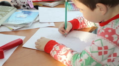 child draws sitting at the table - stock footage