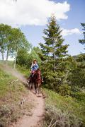 Stock Photo of Woman horse riding through Beaver Creek, Colorado, USA
