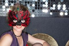 Woman wearing feather mask in bar - stock photo