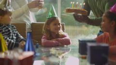 4K Little girl celebrating her birthday with a cake & happy family & friends Stock Footage