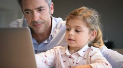 Man with little girl using laptop computer - stock footage