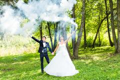 Wedding, love, relationships, marriage. Smiling bride and groom with blue smoke - stock photo