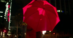 Couple kissing behind a red umbrella in town Stock Footage