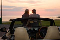 Couple admiring sunset in convertible Stock Photos