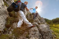 Father and son hiking on rocky terrain Stock Photos