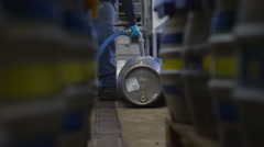 4K Worker in a brewery filling barrels of beer with a hose.  - stock footage