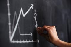 Increasing graph of currency rate drawn by hand on blackboard Stock Photos