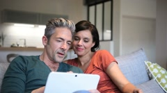 Couple choosing tv program on digital tablet - stock footage