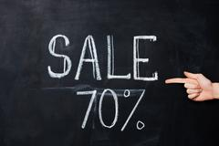 Hand pointing at seventy percent sale drawn on blackboard Stock Photos