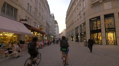 Walking and riding bikes on Bognergasse near Prada store, Vienna Stock Footage