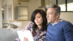 Couple at home websurfing with digital tablet - stock footage