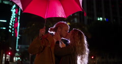 Couple kissing under a red umbrella in town Stock Footage