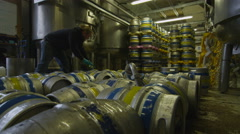 4K Worker in a brewery filling barrels of beer with a hose Stock Footage
