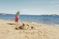 Child making moat around sandcastle Stock Photos